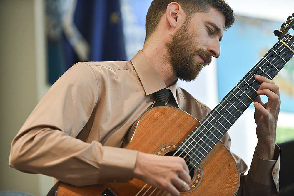 Photo by Rashah McChesney/Peninsula Clarion Armin Abdihodzic, a classical guitarist, plays on Wednesday August 5, 2015 at the Kenai Chamber of Commerce and Visitors Center in Kenai, Alaska. Abdihodzic played during the Noontime Tunes concert series for the Kenai Peninsula Orchestra's Summer Music Festival.